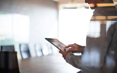 Homme qui regarde une tablette dans une salle de réunion