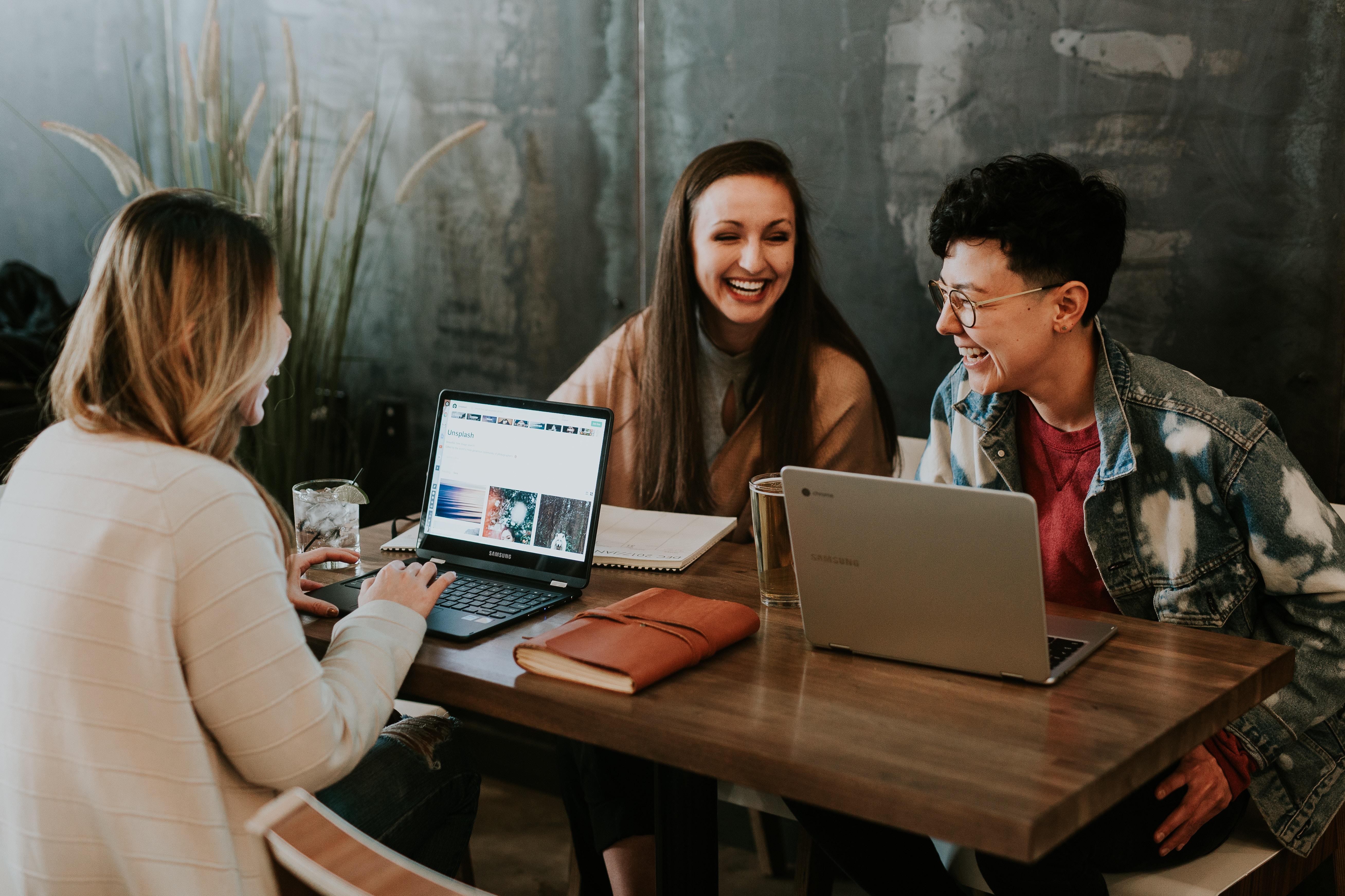 trois personnes autour d'une table avec ordinateur qui rigolent