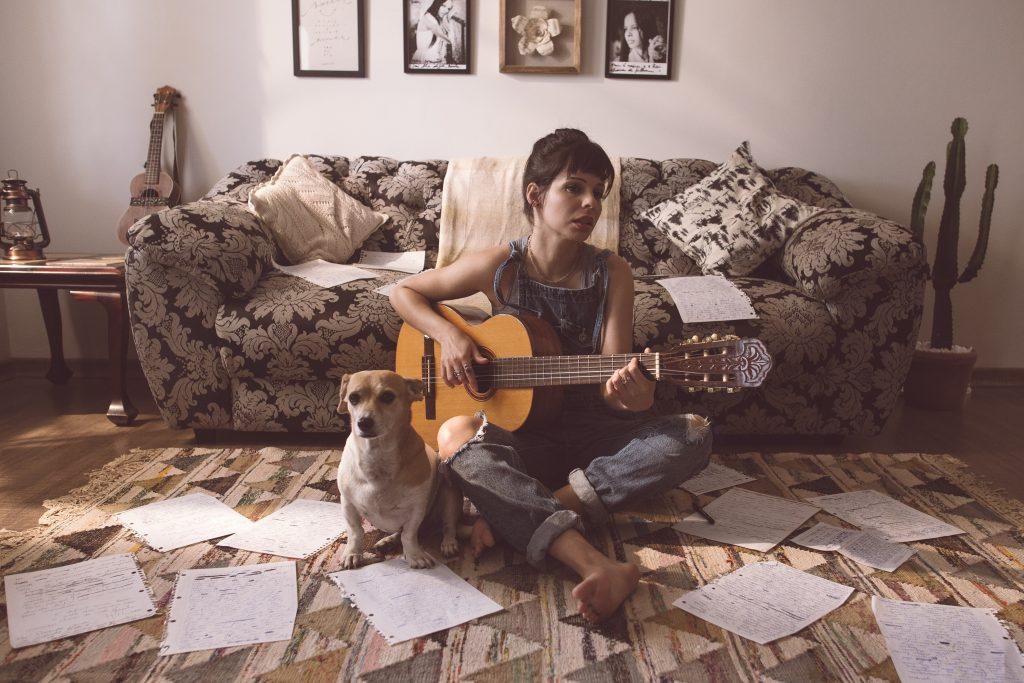 Un femme faisant de la guitare avec son chien